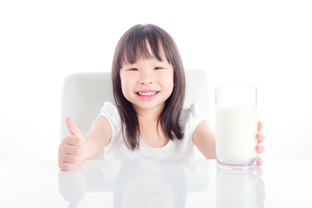 Little asian girl holding a glass of milk and showing thumb up over white background Stock Photo