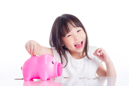 Little asian girl putting coin into pink piggy bank over white background