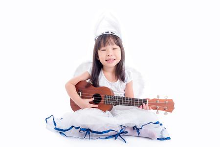 Little asian girl playing ukulele on the floor Stock Photo