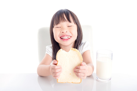Little asian girl eating bread with a glass of milk for breakfast over white background Stock Photo