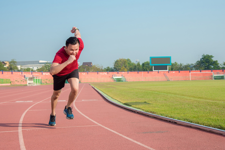 Young asian sporty man running in sport complex center