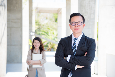 Young asian businessman wearing suit and smile with businesswoman and modern building in background Stock Photo
