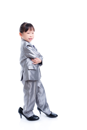 Full length of little asian girl wearing suit and big high heel shoes standing over white background Stock Photo