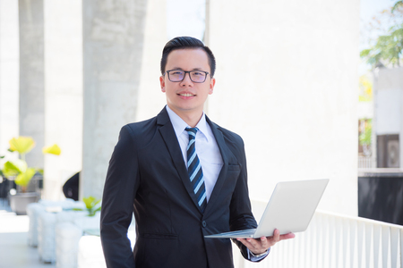 Young asian businessman wearing suit using laptop computer outdoors Stock Photo