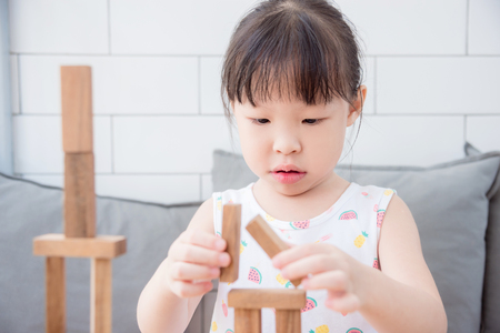 Little asian girl playing wooden blocks at home Stock Photo