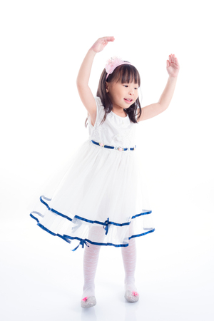 Little asian girl in white dress dancing over white background Stock Photo