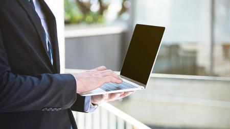 Hands of a businessman using laptop computer outdoor