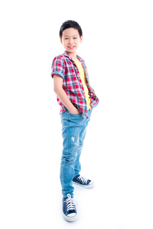 Full length of young asian boy standing and smiles over white background