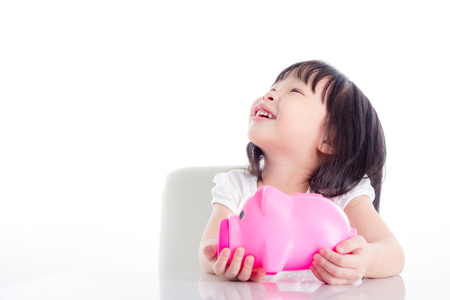 Little asian girl holding pink piggy bank and looking up over white background Stock Photo