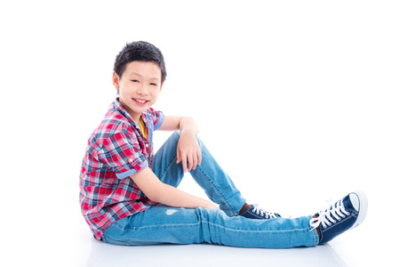 Young asian teenager boy sitting and smiles over white background