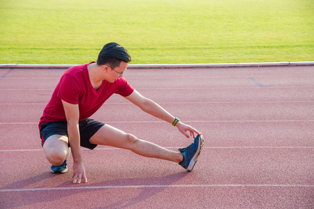 Young asian sport man stretching his leg muscle before running