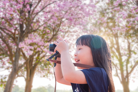 Little asian girl taking photo by camera in pink blooming flower park