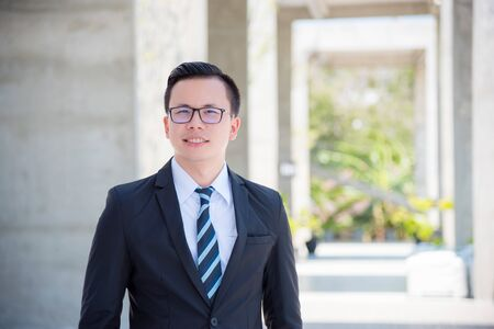 Young asian businessman wearing suit and smile on modern buiding background Stock Photo