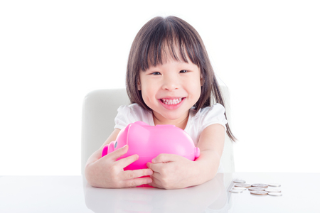 Little asian girl hugging pink piggy bank over white background