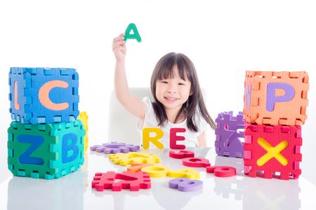 petite fille asiatique jouant jouet d & # 39 ; alphabet sur fond blanc