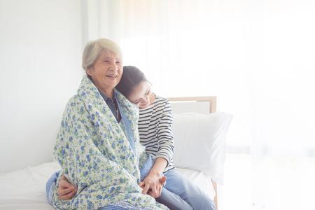 Asiatische Tochter, die ihre ältere Mutter im Schlafzimmer zu Hause umarmt Standard-Bild