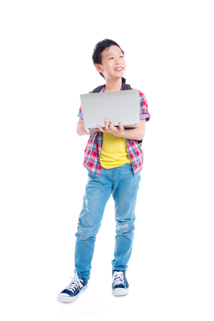 Full length of young asian boy standing and using notebook computer over white background