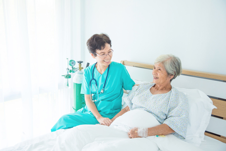 Senior asian female patient smiling with nurse who come to visit her at bed