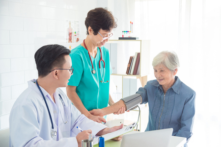 Asian doctor and nurse checking senior woman blood pressure at hospital Stock Photo