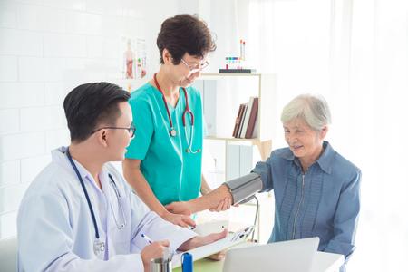 Médico y enfermera asiáticos controlando la presión arterial de la mujer mayor en el hospital Foto de archivo