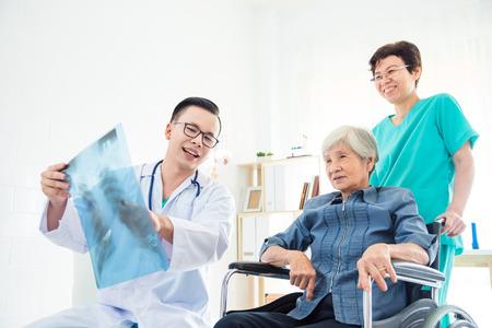 Aziatische arts legt het resultaat van de röntgenfoto uit aan zijn patiënt in het ziekenhuis
