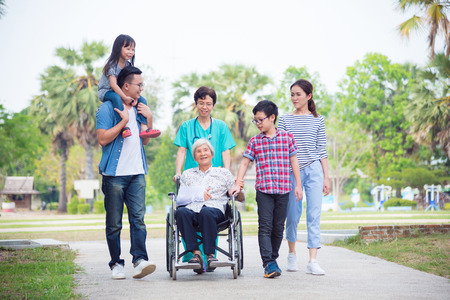 Senior female patient sitting on wheelchair with her family and nurse in hospital park