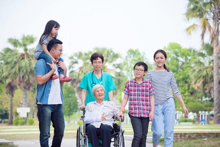 Senior femminile paziente seduto sulla sedia a rotelle con la sua famiglia e l'infermiera nel parco dell'ospedale