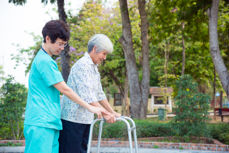 Asian nurse helping senior female patient walking by walker support Archivio Fotografico