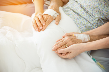 Daughter and nurse holding senior female patients hands Stock Photo