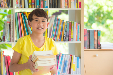 Young asian boy holding books and smiles in library Stock Photo