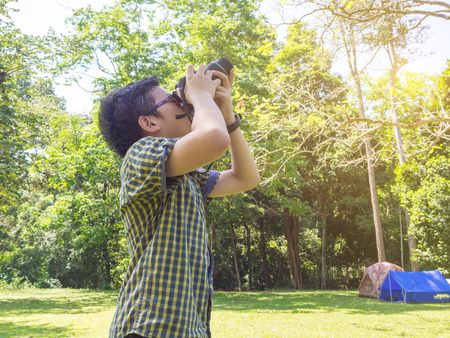 Young asian boy taking photo by camera at camping site in forest