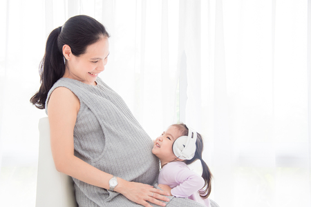 Little asian girl wearing headset and smiling with her pregnant