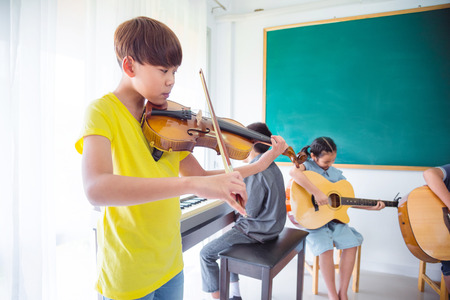 Young asian boy playing violin with friends in music classroom