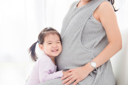 Little asian girl listening sound from her pregnant mother's belly