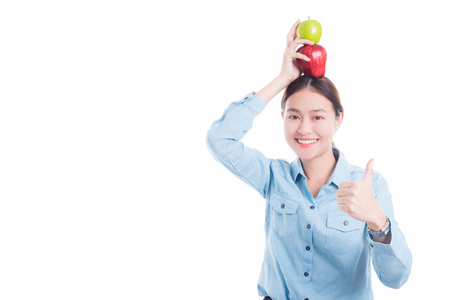 Beautiful asian woman holding apples and smiles over white background