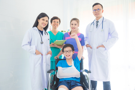 Group of medical team standing with young boy patient sitting on wheel chair and smile. Stock Photo