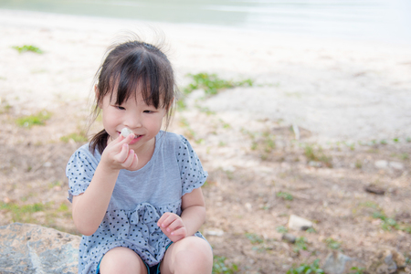 Little asian girl sitting on beach, looking at shell and smile Stock Photo