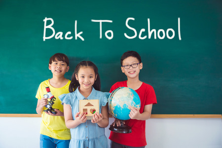 Three asian student smiling in front of chalkboard with textBack to school