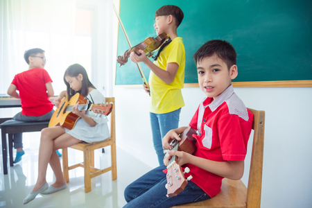 Young asian boy playing ukulele with friends in music classroom Imagens