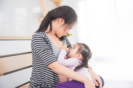 Beautiful asian woman breast feeding her daughter at home