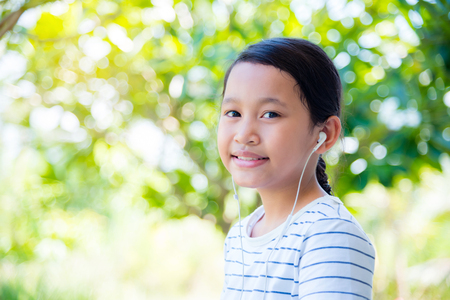 Pretty asian girl wearing headset and smiles in park Stock Photo
