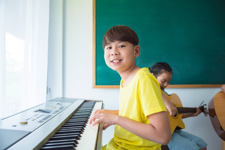 Young asian boy playing music keyboard at school Stock Photo