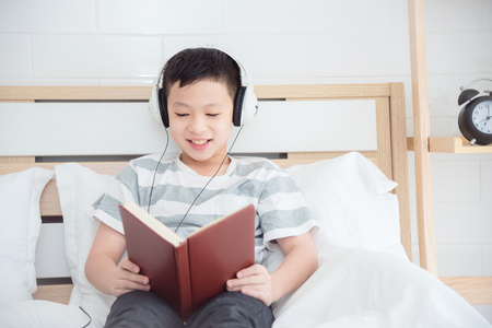 Young asian boy wearing headset and reading book on bed Stock Photo