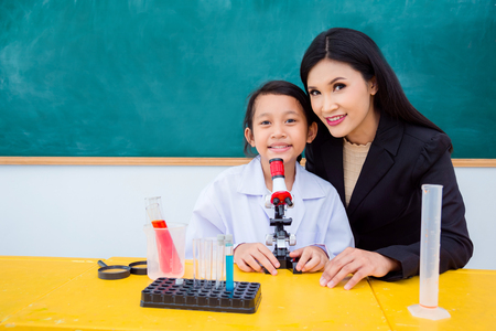Asian schoolgirl and beautiful teacher sitting and smiling in school classroom Stock Photo