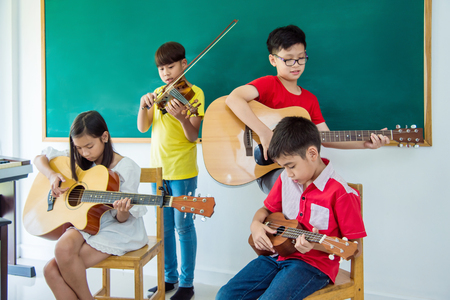 Young asian children playing music instruments in music classroom