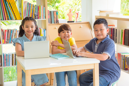 Three of asian student smiling in school library Stock Photo