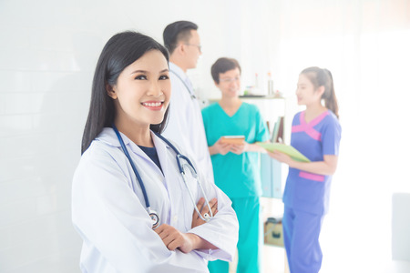 Asian female doctor smiling and looking at camera while medical team meeting on background