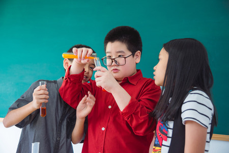 Young asian school children doing chemistry experiment in classroom