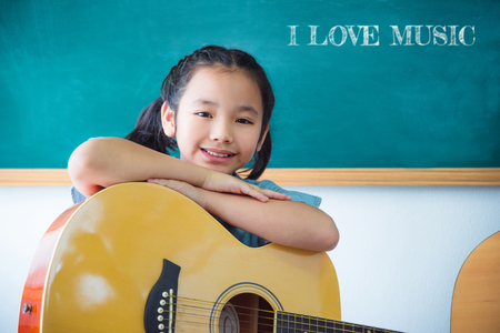 Pretty asian girl smiling with guitar in school classroom