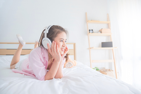 Young asian beautiful woman listening music on bed